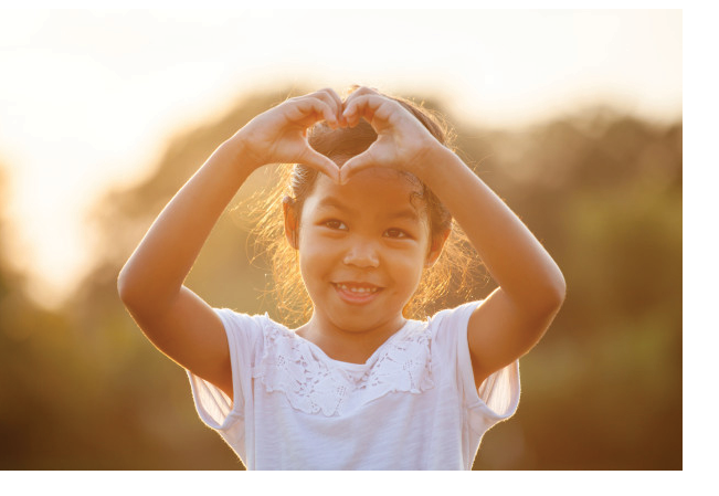 cute-asian-child-girl-making-heart-shape-with-hands-field-with-sunlight_7186-2927